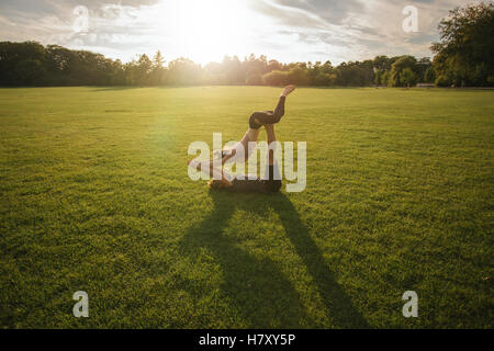 Outdoor shot of young man and woman doing yoga in pair. Couple doing acrobatic yoga workout on lawn. - Stock Photo