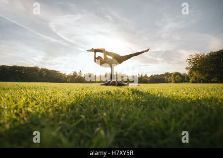 Fit young couple doing acro yoga. Man lying on grass and balancing woman in his feet. Acrobatic balance in park.
