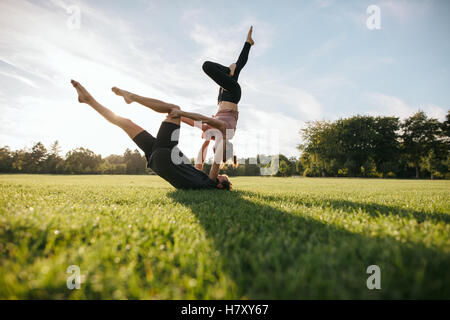 Healthy young couple doing acro yoga on grass. Man and woman doing various yoga poses in pair outdoors at the park. - Stock Photo
