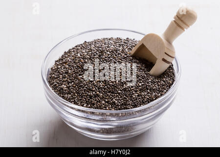 natural organic dry chia seeds in glass bowl with scoop - Stock Photo