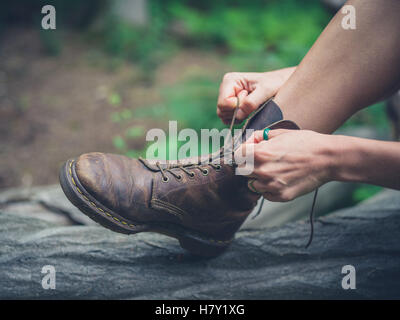 A young woman is sitting on a log in the forest and is tying her boots - Stock Photo