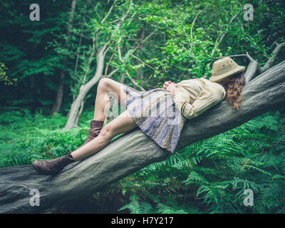 A young woman is lying on a fallen tree in the forest surrounded by ferns with a safari hat covering her face - Stock Photo