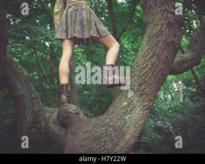 A young woman wearing a skirt is standing in a tree in the forest - Stock Photo