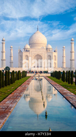 Distant telephoto front centered view of Taj Mahal and compressed long water fountain in foreground on clear blue - Stock Photo