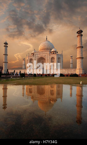 Iconic Taj Mahal and colorful sunset sky reflected in a puddle of water on front lawn in evening at Agra, Uttar - Stock Photo