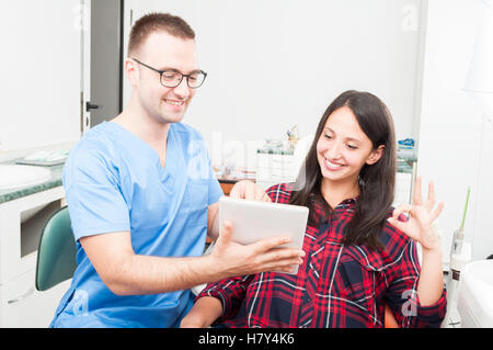 Dentist with patient showing something on tablet and showing okay gesture - Stock Photo