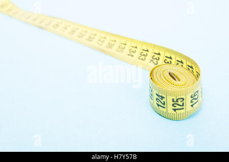 Closeup of tapeline on blue background with copy space area - Stock Photo