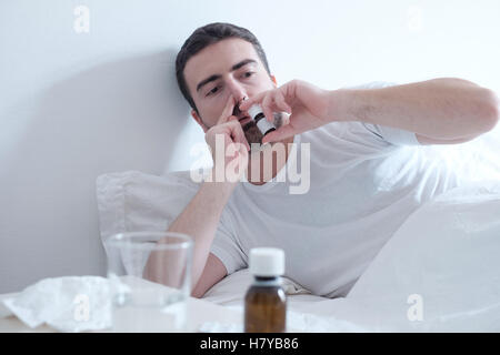 Man feeling cold and using a nasal spray lying in the bed - Stock Photo