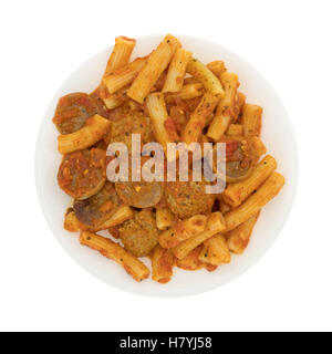 Top view of a serving of rigatoni pasta with sausage and meatballs in a marinara sauce on a plate isolated on a - Stock Photo