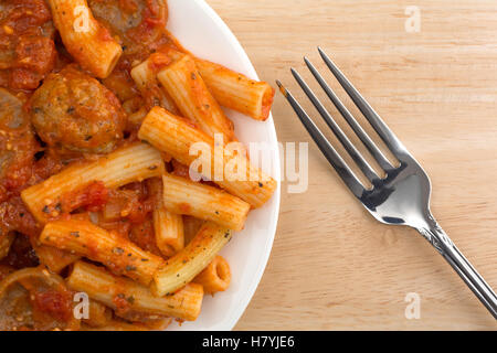 Top close view of a serving of rigatoni pasta with sausage and meatballs in a marinara sauce on a plate with a fork - Stock Photo