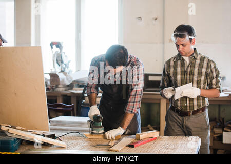 two man polishes boards. carpenter with a sander - Stock Photo