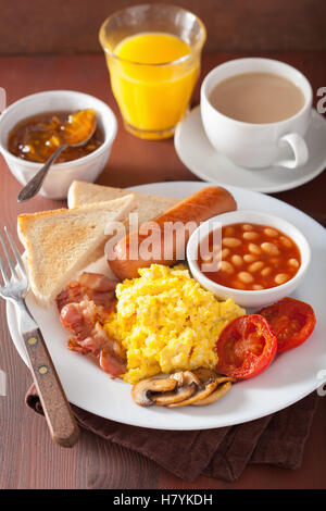 full english breakfast with scrambled eggs, bacon, sausage, beans, tomato - Stock Photo