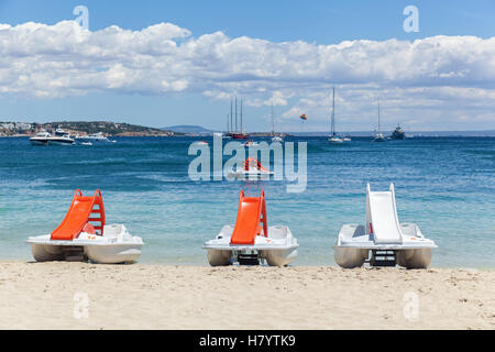 Boats in the bay. Three catamarans on the sandy beach with the beautiful Spanish seascape on the background. - Stock Photo