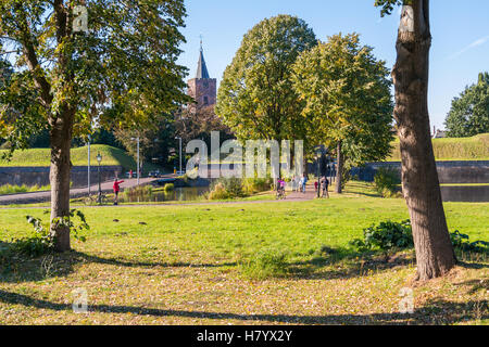 Autumn in old fortified town of Naarden with people, church tower and rampart, Netherlands - Stock Photo