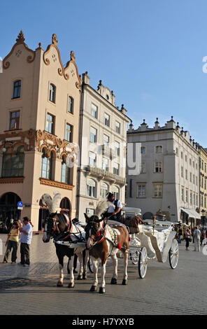 Horse-drawn carriage in Main Market Square, Rynek Glowny, in Krakow, Cracow, Poland, Europe - Stock Photo