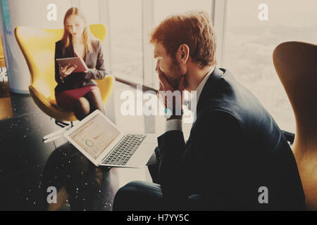 Bearded thoughtful man entrepreneur in formal business suite sitting on yellow armchair with laptop with diagrams - Stock Photo