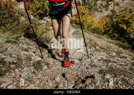 closeup feet  runner athlete and walking sticks on a mountain trail - Stock Photo