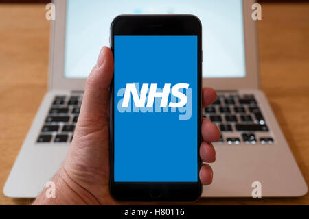 Using iPhone smartphone to display logo of NHS , National Health Service website - Stock Photo