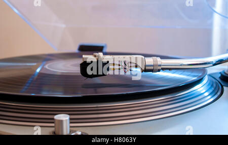 Close up of a turntable needle head playing music from an lp.  (shallow focus). - Stock Photo