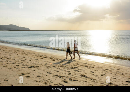 Mature couple walking on the beach and Golden Beautiful sky light reflecting on Ocean. - Stock Photo