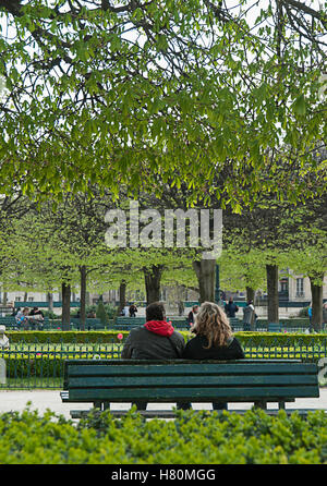 A couple sitting on a bench at the Jardin du Palais Royal, Paris, France - Stock Photo