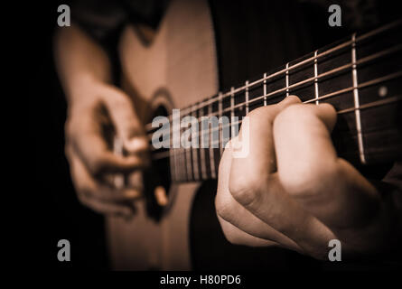 Close up of hands on the strings of a guitar, France - Stock Photo