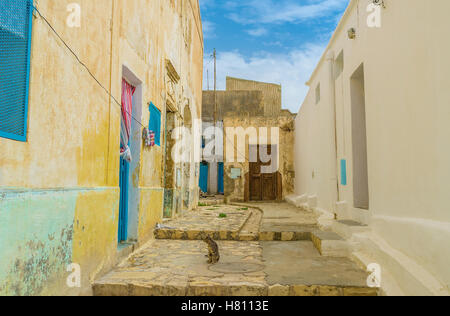 The small yard in old residential neighborhood of El Kef with crumbling walls and wooden doors, Tunisia. - Stock Photo
