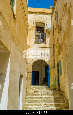 The tiny lane ends with the staircase to the old house, El Kef, Tunisia. - Stock Photo