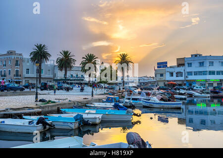 The beautiful sunset over the old port reflects in water - Stock Photo
