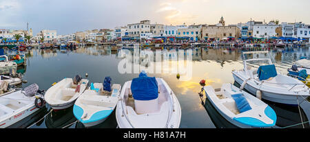 The scenic sunset reflects in water between the boats - Stock Photo