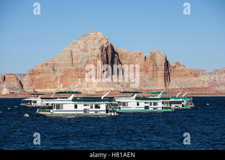 Desert sandstone peaks and houseboats on Lake Powell in the Glen Canyon National Recreation Area. - Stock Photo