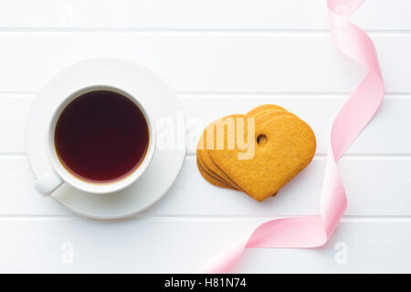 Gingerbread hearts and cup of coffee on white table. Top view. - Stock Photo