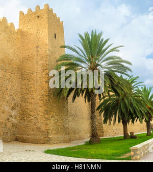 The ramparts of Sousse surrounded by green gardens with palms, Tunisia. - Stock Photo