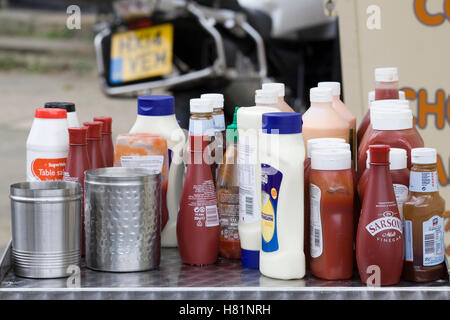 Group of sauces on a table at a burger bar, multiple bottles of ketchup HP Sauce,  salt pepper and Mayonnaise - Stock Photo