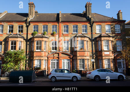 Front view of a classic English Victorian property with three floors of apartments with cars parked in front of - Stock Photo