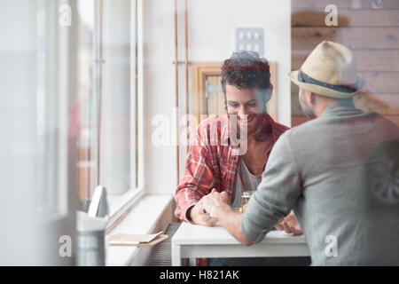 Gay couple sat holding hands in cafe