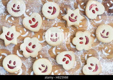 Homemade Jammie Dodgers. Smiling face biscuits and icing sugar impressions on wood - Stock Photo