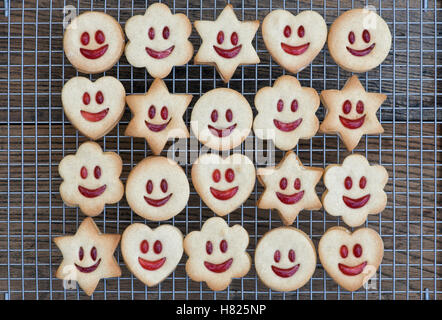 Homemade Jammie Dodgers. Smiling face biscuits faces on a wire rack - Stock Photo