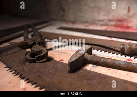 Close up of saws, sickles and other devices on the bloody floor in basement in a Halloween horror concept - Stock Photo