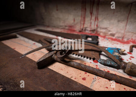 Close up of saws, sickles, hammer and other devices on the bloody floor in basement in a Halloween horror concept - Stock Photo