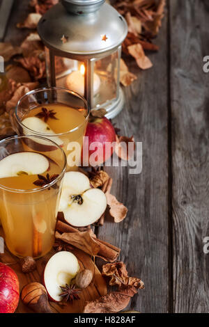 Hot apple cider with cinnamon sticks and spices on fall leaves background - Stock Photo
