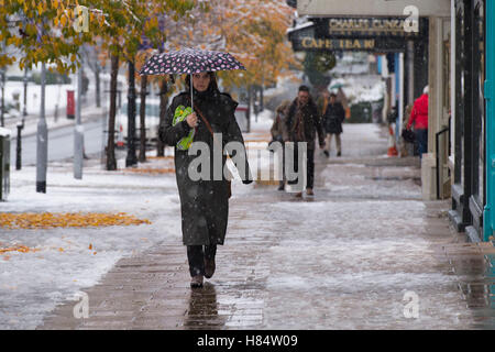 Ilkley, West Yorkshire, UK. 9th November 2016. It is snowing and pedestrians (wearing boots, winter coats and holding - Stock Photo