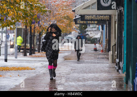Ilkley, West Yorkshire, UK. 9th November 2016. It is snowing and pedestrians (wearing boots, scarves and winter - Stock Photo