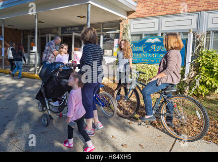 Merrick, New York, USA. Nov. 08, 2016. On Election Day, parents, accompanied by their children, are at Polling Place - Stock Photo