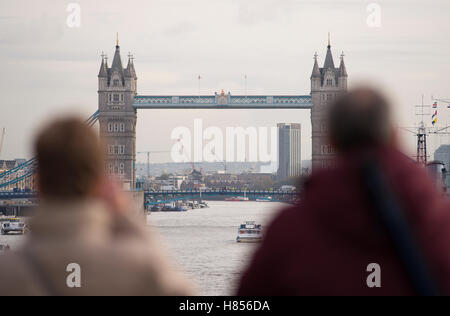 London Bridge, UK. 10th November, 2016. Grey and cold in London as wrapped-up pedestrians on London Bridge watch - Stock Photo