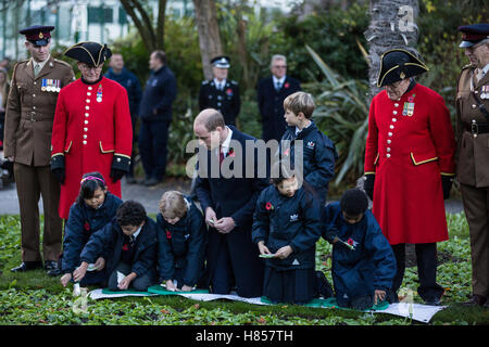 London, UK. 10th November, 2016. The Duke of Cambridge plants poppies with schoolchildren during a visit to Kensington - Stock Photo