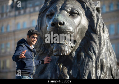 LONDON - OCTOBER 31, 2016: A tourist poses in front of one of the four bronze lions in Trafalgar Square. - Stock Photo