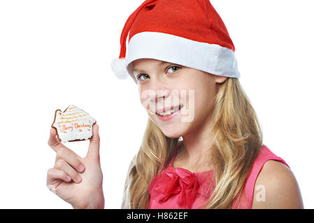 Happy teen girl in red cap with Christmas cookie isolated white - Stock Photo