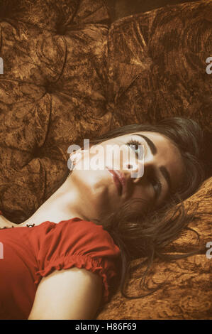 Worried young woman laying down on the sofa looking up - Stock Photo