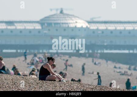 People enjoying the spring weather on Brighton beach - Stock Photo